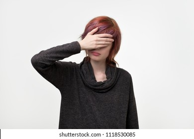 Portrait of unusual informal pretty woman with colorful hairstyle covering her face with hand. Try to ignore every day problems. Hide your emotion from other people.