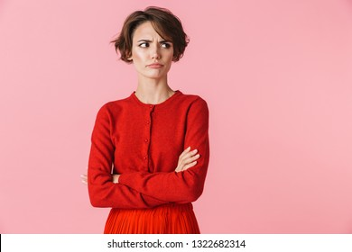 Portrait of an upset beautiful young woman wearing red clothes standing isolated over pink background