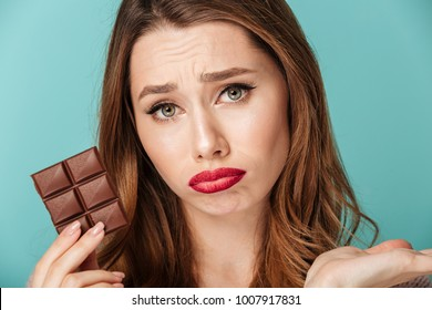 Portrait of an upset brown haired woman with bright makeup holding chocolate bar isolated over blue background