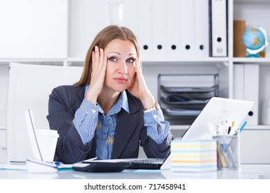 Portrait of upset businesswoman with headache working on laptop in office