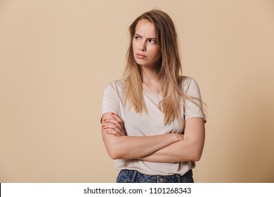 Portrait of an upset casual girl with arms folded looking away isolated over beige background