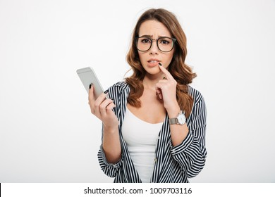 Portrait of an upset casual girl holding mobile phone and looking at camera isolated over white background
