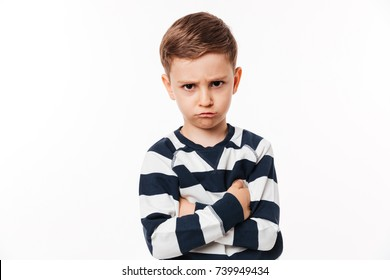 Portrait of an upset cute little kid standing with arms folded and looking at camera isolated over white background