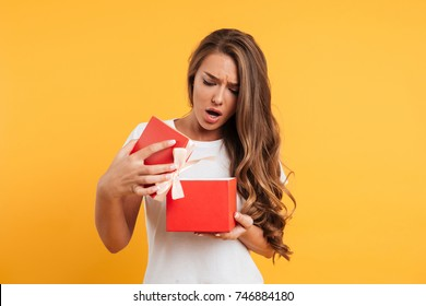Portrait of an upset disappointed girl opening gift box isolated over yellow background