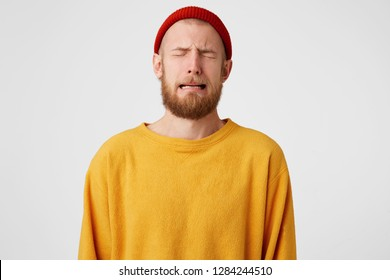 Portrait of upset distressed sobbing crying guy. Bearded man crying a river because of love, isolated over whire background