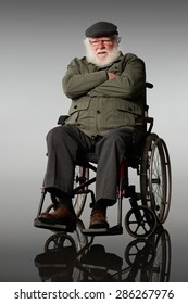 Portrait of upset elderly man sitting on a wheelchair with his arms crossed over grey background