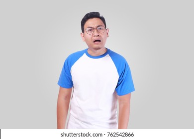 Portrait of upset hopeless young Asian man in white shirt frowning eyebrows and looking at camera with disappointed shocked surprised gesture while standing over grey background