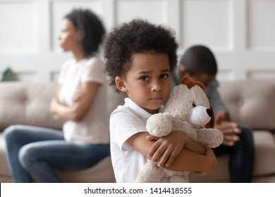 Portrait of upset little african child boy holding toy looking at camera, sad sensitive small mixed race kid feel lonely hurt suffer from family conflicts fights, parents divorce, children custody