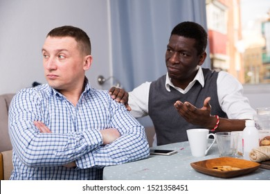 Portrait upset man looking away after conflict, friend tries reconcile