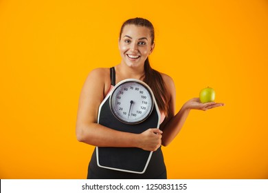 Portrait of an upset overweight young woman wearing sport clothing standing isolated over yellow background, holding green apple and scales
