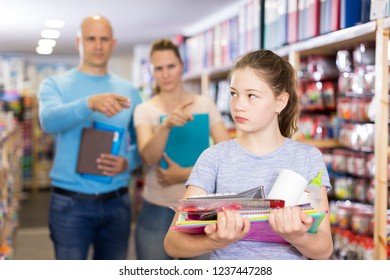 Portrait of upset preteen girl with school supplies scolded by parents in stationery shop