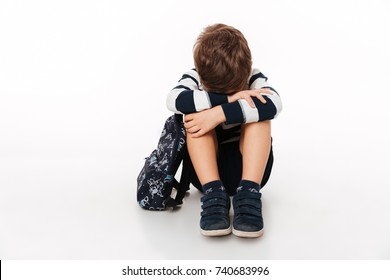 Portrait of an upset sad little kid with backpack sitting on a flor and crying isolated over white background