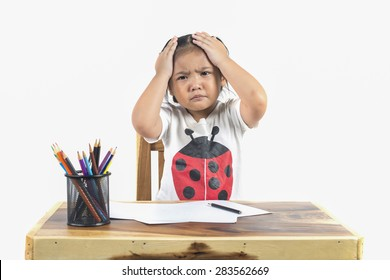 Portrait of upset schoolgirl sitting at desk with books holding his head