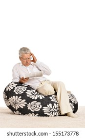 Portrait of upset senior man reading newspaper in armchair