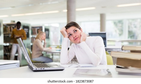 Portrait of upset tired female student preparing for exam in university library. High quality photo