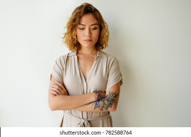 Portrait of upset young Asian woman in studio