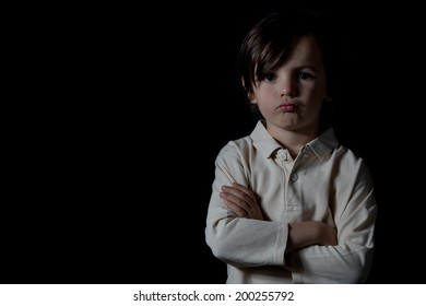 Portrait of upset young boy, black background.