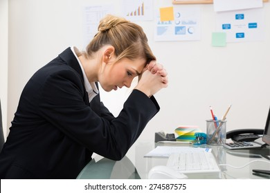 Portrait Of Upset Young Businesswoman Sitting At Desk In Office