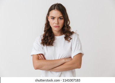 Portrait of an upset young casual brunette woman standing with arms folded isolated over white background