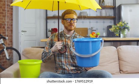 Portrait of upset young hipster guy in glasses sitting on couch at home under umbrella holding plastic bucket collecting water falling from ceiling. Waiting for repairman