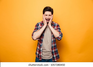 Portrait of an upset young man crying isolated over yellow background