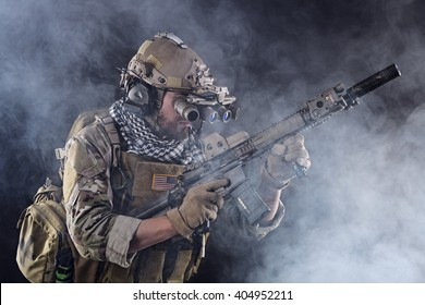 Portrait of US Army Soldier with Four-eyed night vision goggles in the Smoke; Dark and Foggy Background