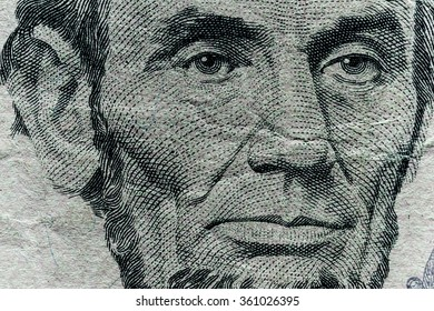 Portrait of USA President Abraham Lincoln on five-dollar bill .