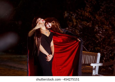 Portrait of a vampire girl drinking blood of victim at outdoors winter background. Halloween concept.
