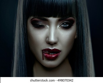 Portrait of vampire look of  woman for halloween,wearing long black hair, dark, bright make up,blinking and liking the blood drop in the corner of her mouth