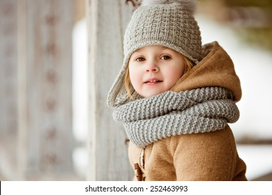 portrait of a very cute beautiful girl child in a beige coat and a gray hat, close up