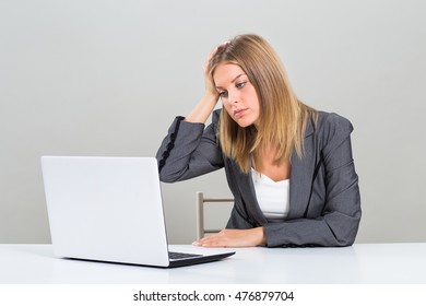 Portrait of very despair businesswoman looking at her laptop and sitting at the table.Despair businesswoman looking at laptop