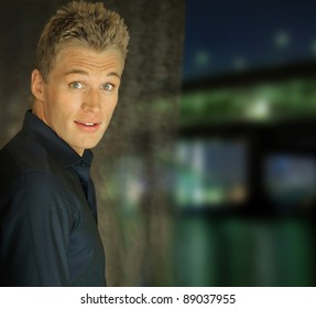Portrait of very good-looking blond man standing in front of a window revealing a river and bridge