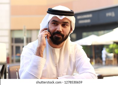Portrait Of A Very Handsome Rich Arab Business Man Happy Speaking In Phone And Wearing UAE Traditional Dress  ( UNITED ARAB EMIRATES EMIRATI KANDORA )