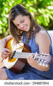 Portrait of very handsome teenager playing guitar in her garden