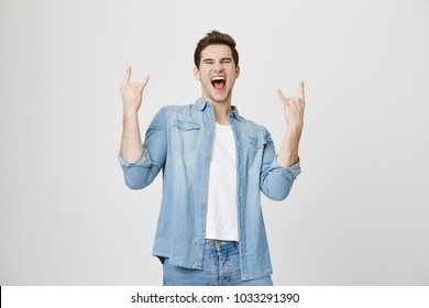 Portrait of very happy attractive european adult showing rock signs with both hands and shouting out loud, expressing overwhelmingness and joy, isolated over white background.