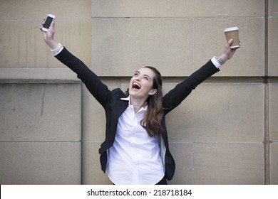 Portrait of a very happy caucasian businesswoman celebrating good news. Business woman with arms up in the air cheering.