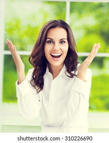 Portrait of very happy gesturing young brunette businesswoman with at office. Success in business concept.