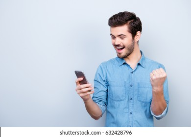 Portrait of very happy hansome brunet reading a message on his pda and celebrating victory