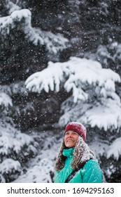 A portrait of a very happy woman enjoying a cold and snowy day in the forest