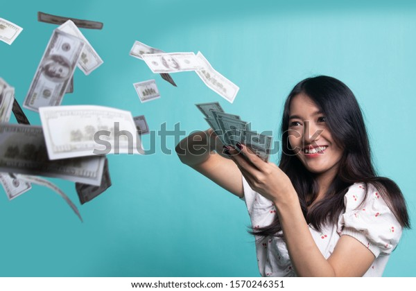 Portrait of very happy  young asian woman throwing out money banknotes on cyan color background