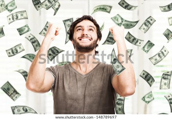 Retrato de un joven muy feliz bajo una lluvia de dinero