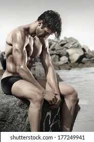 Portrait of a very muscular young man at beach sitting on rock looking down