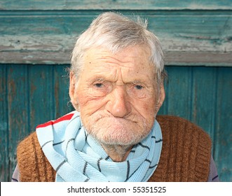 A portrait of a very old man, 96 years old near his house.