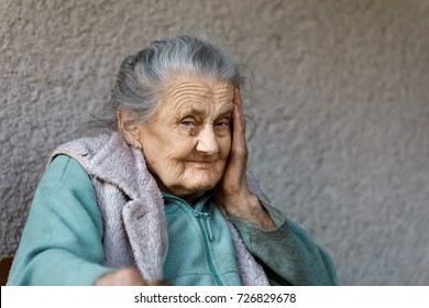 Portrait of a very old and tired of life wrinkled woman outdoors with a hand near her face