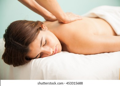 Portrait of a very relaxed young woman with her eyes closed getting a back massage at a wellness center