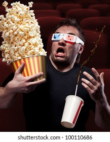 Portrait of very scared man watching 3D movie, drinking cola and eating popcorn