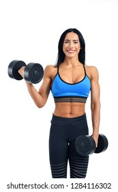 Portrait of very strong and young woman working regularly in gym under her body. Smiling athlete in sportswear holding dumbbells and demonstrating power. Personal trainer offering help for everyone.