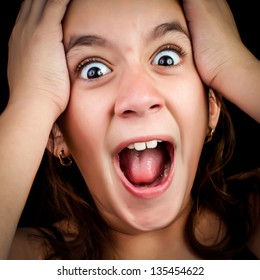 Portrait of a very surprised or scared girl screaming loudly with her hands on her head isolated on a black background