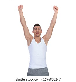 portrait of victorious fitness man looking up while standing on white background and celebrating with fists in the air
