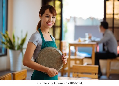 Portrait of Vietnamese beautiful waitress with a tray standing in a cafe